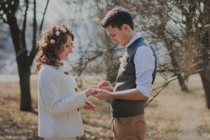 Man putting ring onto girlfriend's hand in a field