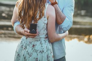 Man hugging girlfriend with ring behind her after proposal closeup