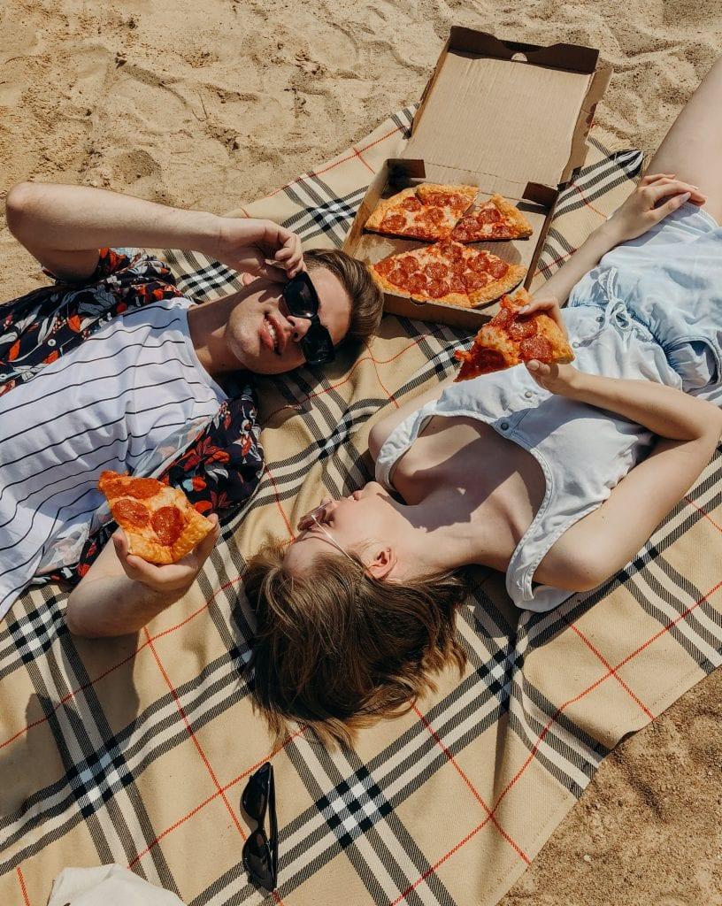 couple eating pizza on beach